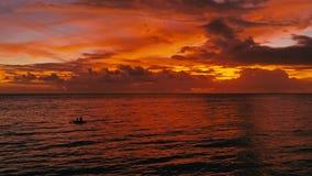 Overweldigend mooi luchthommelbeeld van een rode tropische zonsondergang boven de overzeese oceaan met tweepersoons in een kano v stock afbeeldingen