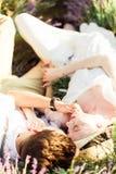 Overweldigend portret van de bruid en de bruidegom die in een lavendelgebied liggen stock afbeelding