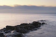 Overweldigend zonsopganglandschap over rotsen in overzees Royalty-vrije Stock Afbeeldingen