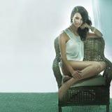 Overweldigende donkerbruine schoonheidszitting op een stoel Stock Afbeeldingen