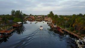 Overweldigende lucht4k mening over kleine toeristenboot die langzaam in het kalme diepe blauwe water van de kanaalrivier in tropi stock video