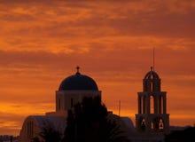 Overweldigende Oranje Gradatie van de Zonsondergangnagloeiing over een Kerk in Santorini, Griekenland Stock Foto