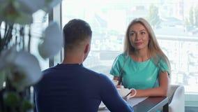 Overweldigende vrouw die samen aan haar vriend spreken, die ontbijt hebben bij koffie stock footage