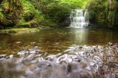 Overweldigende waterval die over rotsen in bos stroomt Stock Afbeeldingen