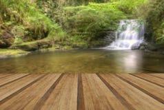 Overweldigende waterval die over rotsen door weelderig groen bos vloeien Stock Fotografie