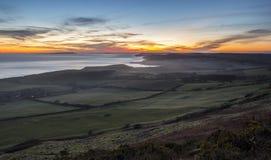 Overweldigende zonsondergang op dramatische kustlijn Stock Foto