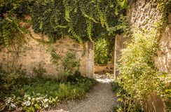 Overwelfde galerijpoort en historische steenmuur in het tuinhoekje Stock Fotografie