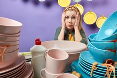 Overwelmed young emotional blonde woman ia sfraid of used cutlery. Overwelmed young emotional blonde woman with hands on her cheeks cannot understandhow to start stock images