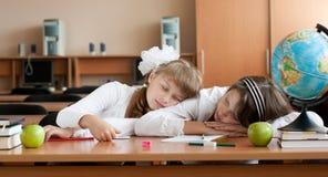 Overwerkte twee preteen schoolmeisjes slapen Stock Foto's