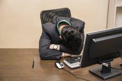 Overwerkte, vermoeide jonge zakenmanslaap in bureau Stock Fotografie