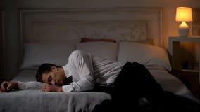 Overwerkte vermoeide mens die in kostuum op bed in uitputting, enig werkverslaafde liggen stock afbeeldingen