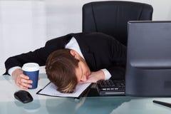 Overwerkte zakenman die op contractdocument rusten stock foto