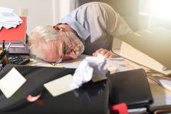 Overwerkte zakenmanslaap op een slordig bureau, lichteffect Stock Afbeelding