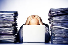 Overwhelmed. Male businessman sitting behind a laptop, his face hidden, with his hands on top of his head.  Two large piles of paperwork are piled on each side Royalty Free Stock Image