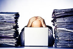 Overwhelmed. Male businessman sitting behind a laptop, his face hidden, with his hands on top of his head.  Two large piles of paperwork are piled on each side Royalty Free Stock Photos