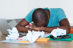 Sleeping african american man at desk at home office. Overwhelmed african american man sleeping at desk at home office Royalty Free Stock Photography