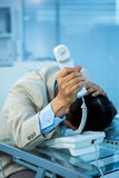 Overwhelmed asian businessman answering the phone. In office royalty free stock photo