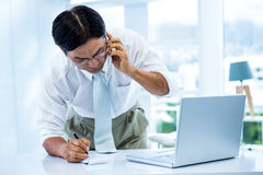 Overwhelmed asian businessman answering the phone and writing Royalty Free Stock Photos