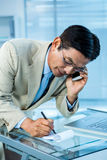 Overwhelmed asian businessman answering the phone and writing. In office Stock Images