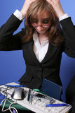 Overwhelmed business woman. Image of a desperate young business woman in front of many office stuff,suggesting confusion and overwhelming work stock photos