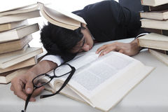 Overwhelmed businessman. To read books sleeping in office Stock Photos