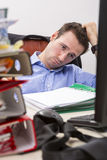 Overwhelmed businessman. Office businessman at his desk full of documents, showing an overwhelmed expression Stock Photography