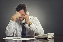 Overwhelmed  businessman with headache. Overwhelmed businessman in white shirt and tie having a headache during a stressful phone conversation. Tired thoughtful Royalty Free Stock Photos