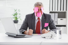 Overwhelmed businessman with sticky notes on head. In his office Royalty Free Stock Photo