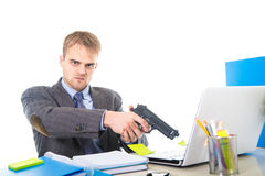 Overwhelmed businessman in upset face expression holding gun pointing computer royalty free stock image