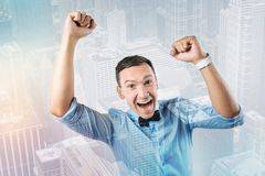 Cheerful excited man holding his hands up. Overwhelmed by emotions. Cheerful excited positive man holding his hands up and smiling while being overwhelmed by Royalty Free Stock Image