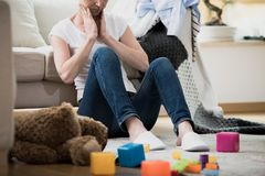 Overwhelmed exhausted tired of cleaning. Overwhelmed exhausted woman feeling tired of cleaning in her messy house sitting on the floor with toys and laundry Stock Images