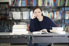 Overwhelmed at the library. Cute female student bored and overwhelmed at a library Stock Images