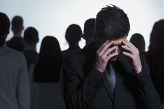 Overwhelmed man against a crowd. Overwhelmed men in a suit standing against a crowd of people Royalty Free Stock Photos