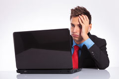 Overwhelmed man at desk. Young business man sitting at desk is overwhelmed of too much work on his laptop Stock Images