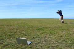 Overwhelmed man running in field away from laptop Stock Photography