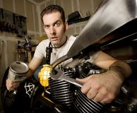 Overwhelmed Mechanic. Overwhelmed man in residential garage working on chopper-style motorcycle Royalty Free Stock Image