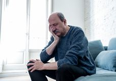 Sad unhappy old senior man suffering from memory loss and alzheimer feeling depressed and lonely. Overwhelmed old senior man suffering alone at home feeling stock photo