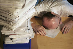 Overwhelmed by Paperwork. A businessman lays his head on the table with weariness as he is overwhelmed by a stack of paperwork.  It must be tax time Royalty Free Stock Image