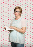 Overwhelmed Pregnant Woman. In eyeglasses reading a book Royalty Free Stock Photos