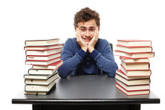Overwhelmed student with face in hands sitting at his desk betwe Stock Image