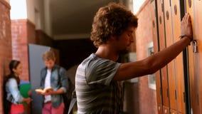 Overwhelmed student leaning against locker stock footage