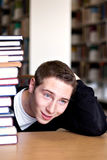 Overwhelmed Student with Piled. An overwhelmed student with a high pile of textbooks he has to go through to do his homework Royalty Free Stock Photos