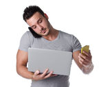 Overwhelmed by technology. Young man with two cell phones and one laptop computer Stock Image