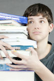 Overwhelmed Teen Holds Stack Of Textbooks Royalty Free Stock Images
