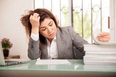 Overwhelmed woman at work. Stressed and overwhelmed young business woman looking at a big pile of documents to review at work Stock Photography
