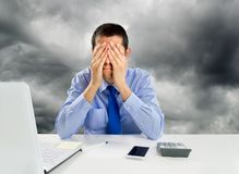 Overwhelmed at the workplace. Man overwhelmed at the office with hands on his face Royalty Free Stock Photo