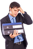 Overwhelmed young businessman holding many folders Royalty Free Stock Photos