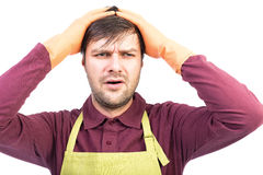 Overwhelmed young man with apron and gloves holding hands on hea Royalty Free Stock Photos