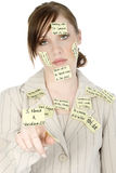 Overwhelmed Young Woman. Young woman with sticky notes all over face. Note up front says I Need A Vacation. Shot in studio royalty free stock photography