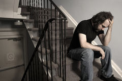 Overwhelming Depression. A male adult with overwhelming depression sitting in the stairwell of his apartment building.  Desaturated Royalty Free Stock Photography